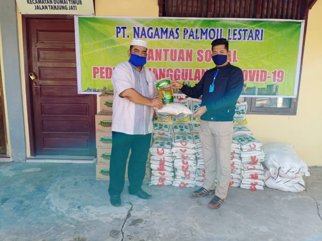 Manager PT Nagamas Palmoil Lestari, Ali Bakri Siregar menyerahkan bantuan paket sembako secara simbolis kepada Lurah Buluh Kasap, Ganda Prawinata